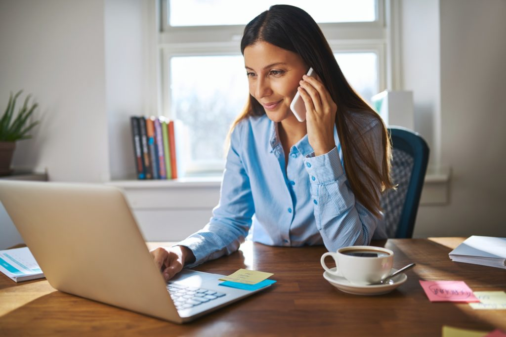 Cute young adult woman on phone behind laptop